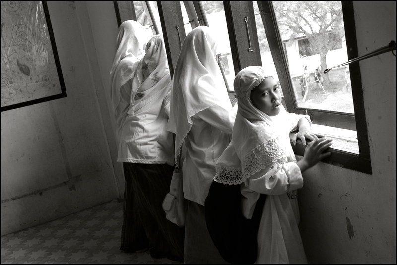 Girls watch the boys outside playing football at an orphanage in Banda Aceh Indonesia