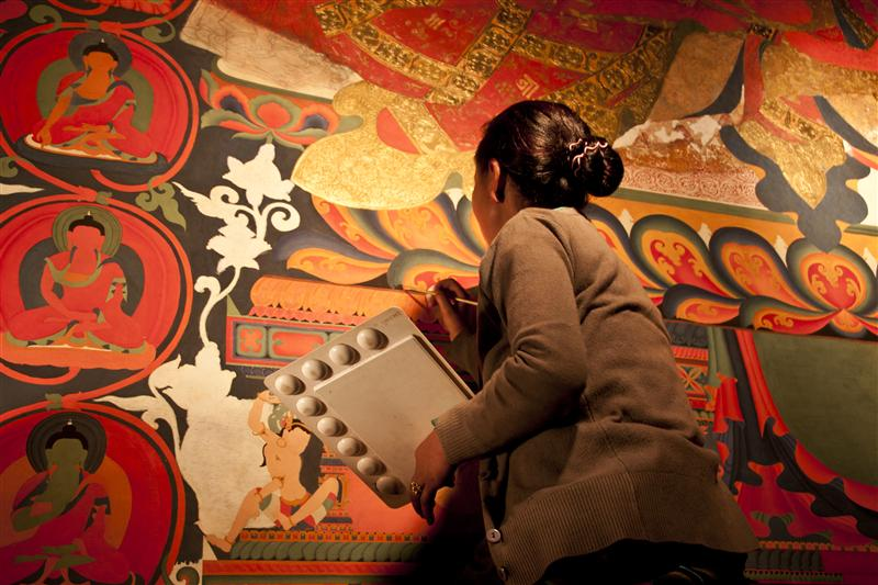 A local Loba woman do the wall paintings inside the Gompa in Lo Manthang.