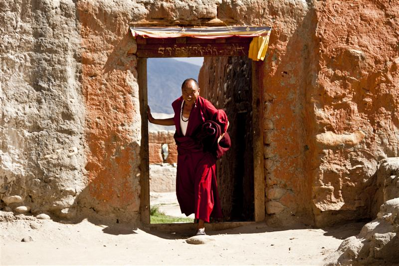 A monk in picture posing as he arrives from the village back to the monastery in Tsarang