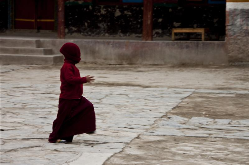A young monk plays inside the monastery complex.