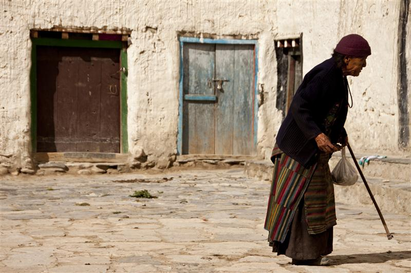 An elderly woman  is seeing outside her house in Upper Mustang