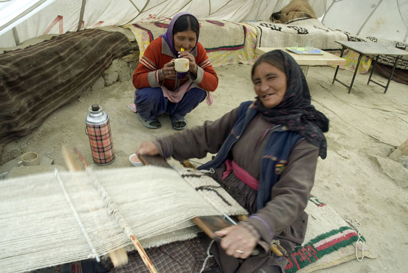 A Changpa woman knitting pashmina with her backstrap loom in her tent