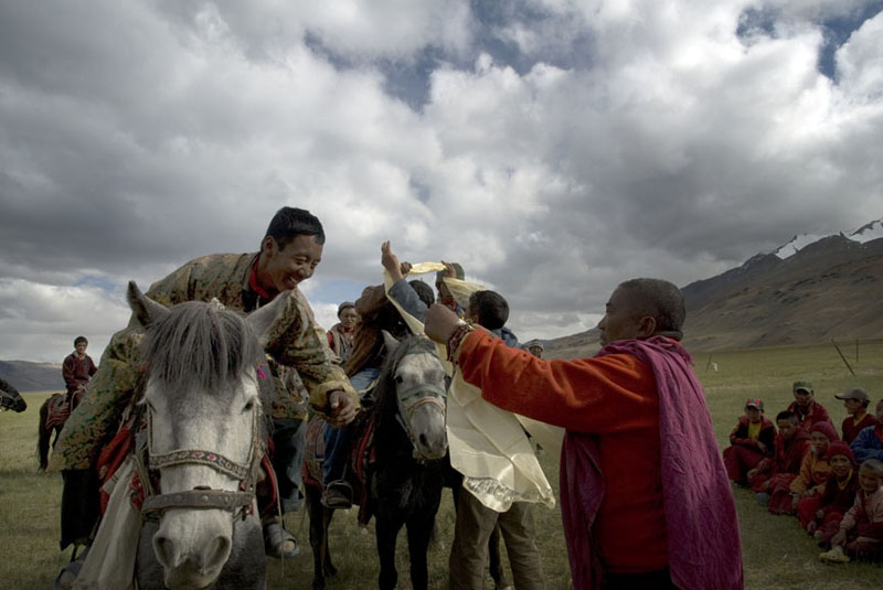 A high monk drapes a kaata, the ceremonial silk scarf,on a Changpa horseman.