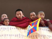 Hopeful monks look their God-king Lama.