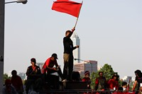 Red shirt protester waves a red flag at the Silom barricade