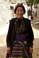 Loba woman in traditional dress stops for a picture while having a walk in the village.