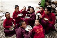 Monks eat together outside the monastery and enjoy their time.