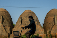 A girl rides her bicycle past one of Sa Dec's brick kilns