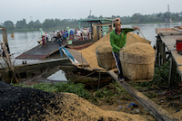 A worker carries a 50kg load of rice husks